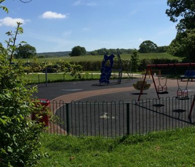 Fenced surfaced play area with swings at Millstream Meadow