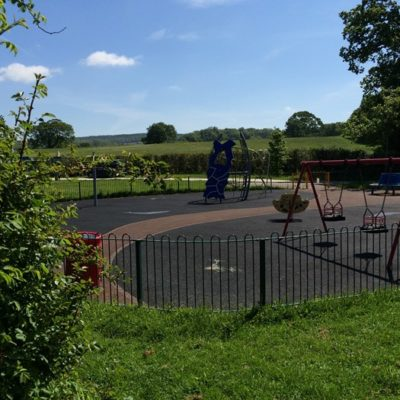 Fenced surfaced play area with swings at Millstream Meadow - Click to open full size image