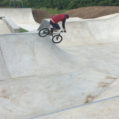 Man on bike in skate park coming down slope - Click to open full size image