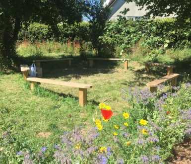 school garden with flower bed and two wooden seating areas