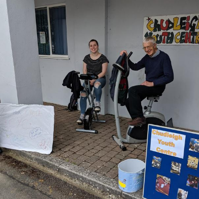 A young woman and an older gentleman sat on exercise bikes
