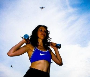 Woman poising against a blue sky holding weights