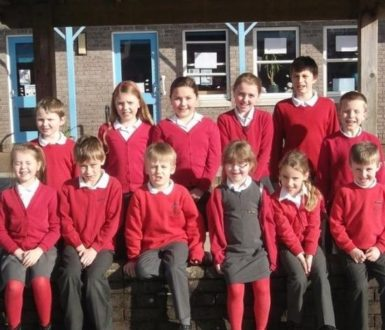 Two rows of children from Chudleigh Primary School in red jumpers