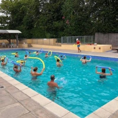 Adults in a swimming pool taking part in a keep fit lesson