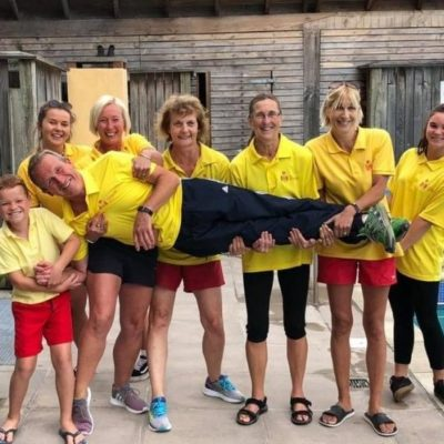 Six adults and one child in lifeguard uniform all smiling