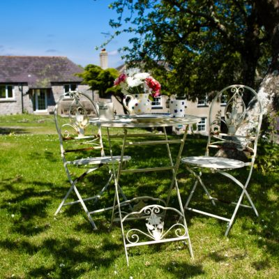 white metal tables and chairs in a garden - Click to open full size image
