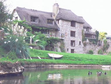 thatched 3 storey cottage overlooking a river with ducks - Click to open full size image