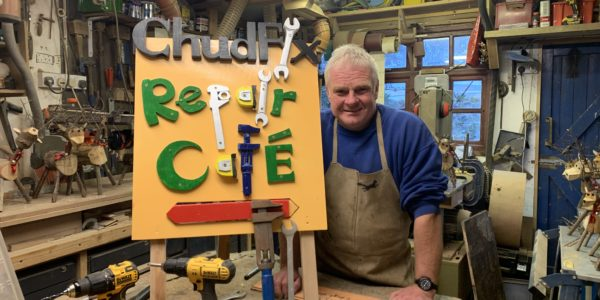 A gentleman in overalls stood next to a home made sign made from recycled materials to promote the Repair Cafe