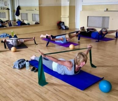 women lying on mats on a sprung wooden floor doing exercises