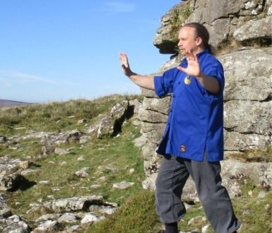 Man in a blue shirt on dartmoor doing T'ai Chi moves
