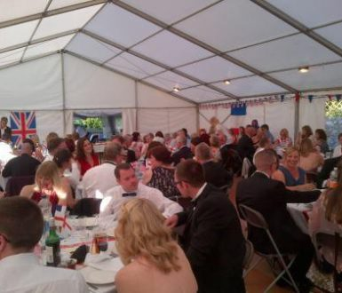 Lots of people sat around tables in evening wear in a marquee