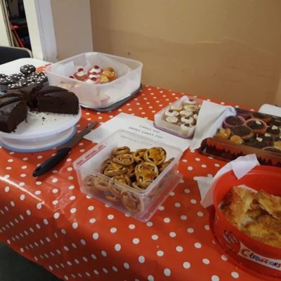 Table laden with different cakes and a red spotty tablecloth