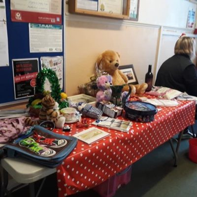 Table displaying lots of different raffle prizes at the coffee morning