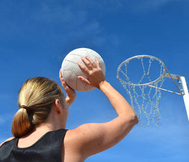 Woman throwing a netball into the net