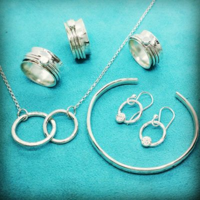 Silver Rings, Earrings And Necklace On A Light Blue Background, From Melanie Bowers Jewellery Shop - Click to open full size image